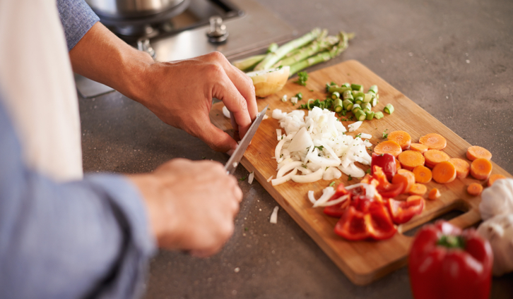 person cutting vegetables with a knife on a cutting board