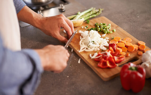person is cutting vegetables on chopping board