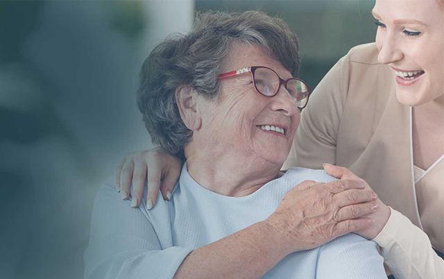 Female nurse and senior female patient smiling off into the distance