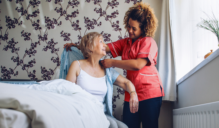 Female nurse dressing a senior female patient sitting on bed