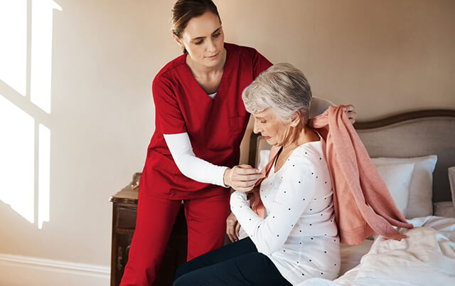 Female PSW assisting senior female patient with getting dressed